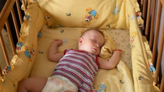 Close up of a little baby boy sleeping, baby lying in baby cot.