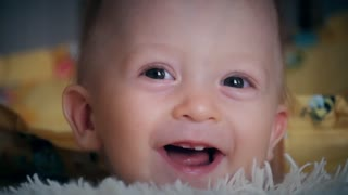 Close up of baby's face while it smiles and laughs. A cute little baby is looking into the camera.