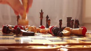 Close up of chess pieces on the board, shallow depth of field. Man playing chess, close-up of hand