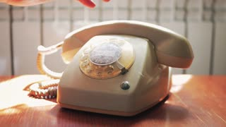 Close up of male hand picking up the receiver of a vintage retro rotary telephone and answering the phone.