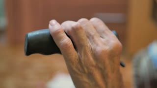 Close up of senior woman hands on walking stick.