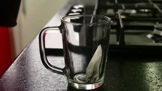 Close up of woman pouring hot water over tea bag in red glass cup.