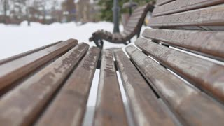 Close-up old wooden bench in the city park in the winter.