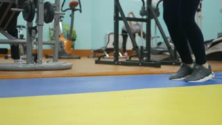 Close up photo of woman's legs. Girl jumping on the skipping rope in gym. Fitness concept. Healthy lifestyle.