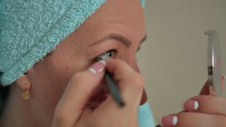 Close up portrait of a young woman with bath towel on head doing her make up looking at the mirror