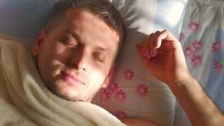 Close-up shot of young man in bed at home sleeping. Wakes up.
