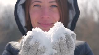 Close up, young woman blowing snow, happy winter time in big city of charming girl having fun in park, enjoying snowfall