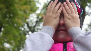 Closeup Of Little Girl Playing Peek-A-Boo With The Camera