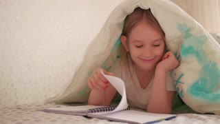 Closeup portrait girl reading book under the blanket and laughing at camera