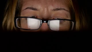 Closeup shot of girl in glasses surfing internet at night.