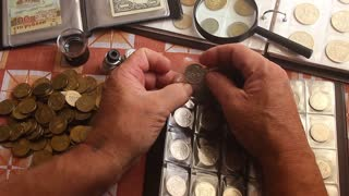 Coin album collection from different countries. Consider coins under a magnifying glass.