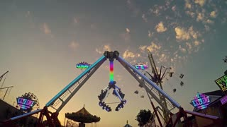 Colorful carousel in motion with sundown in background, people enjoy their ride in the carousel, rotating illuminated attraction ferris wheel.
