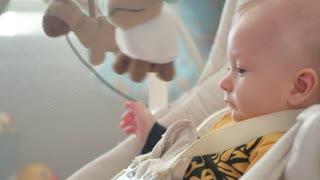 Cute adorable newborn baby boy sitting in swing.