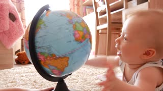 Cute baby plays globe on floor in room, indoor