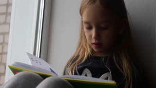 Cute child girl sitting by the window and reading a book in room at home.