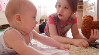 Cute children play with a teddy bear on the floor of the house
