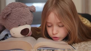 Cute happy little girl with teddy bear and reading book. Pretty kid at home, lying on the floor. Education concept