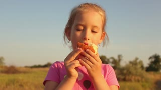 Cute kid girl eating sweet donut outdoor in the park on sunny warm day. Close Up Of Girl Eating Iced Donut.