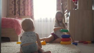 Cute little brother and sister having fun at home. Beautiful sister and small brother playing at home. Educational games for kids.