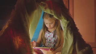 Cute little child is playing with tablet in tent. Happy girl at home. Funny lovely kid having fun in children room.