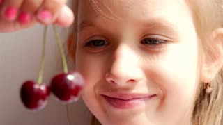 Cute little girl girl eating cherries, close up. Healthy young girl eating red cherries.