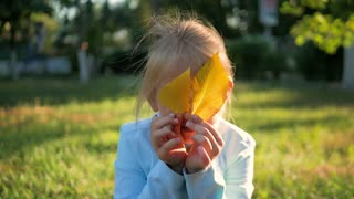Cute little girl hiding over yellow leaves. Autumn portrait smiling child hides her eyes yellow leaves.