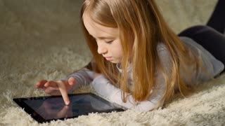 Cute little girl holding digital tablet and smiling while lying in bed. little girl playing on tablet pc. Beautiful girl using tablet while lying on bed.