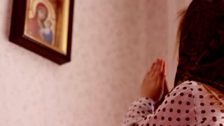 Cute little girl in a headscarf, praying at home in front of the icon. Concept, Russian Orthodox little girl, Christianity.