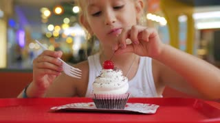 Cute little girl is eating a cake in a cafe.