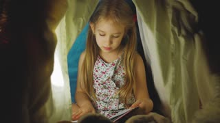 Cute little girl is reading a book in tent. Happy girl plays at home. Funny lovely kid having fun in children room.