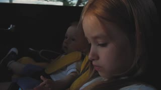 Cute little girl play at smartphone sitting in car seat.