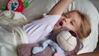 Cute little girl sleeping with teddy bear in bed