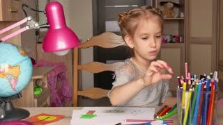 Cute little preschooler child girl drawing at home