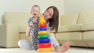 Cute mother and child boy play together indoors at home. Loving mom and baby toddler playing and having fun time together.