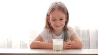Cute preschool girl drinking fresh milk into glass sitting at the table in the kitchen.