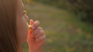 Cute teen girl blowing in whistle outdoor in nature. Close up portrait of a toddler girl blowing a toy whistle outdoors.