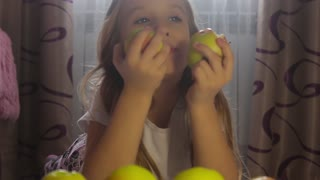 Cute young girl lying in on the floor in his room with apples in front of her counting them. The girl eats apples.