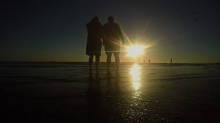 elderly couple taking pics from a beautiful sunset on a tropical beach