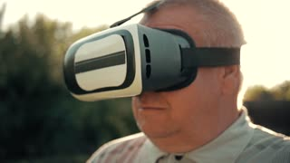 Elderly Man Using Virtual Reality Headset Outdoor.