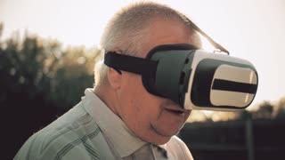 Elderly Man Using Virtual Reality Headset Outdoor.