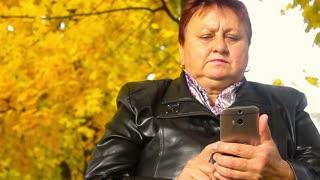 Elderly women with phone in autumn park.