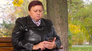 Elderly women with phone in autumn park.