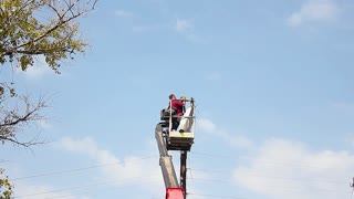 Electric technical repairing street light by boom lift in industrial