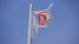 English flag of St George Cross on top of a flagpole, blowing gently in the breeze against a clear blue sky.