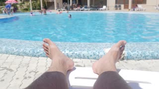 Enjoying summer vacation by the swimming pool, close up of male feet and poolside water on sunny summer day.