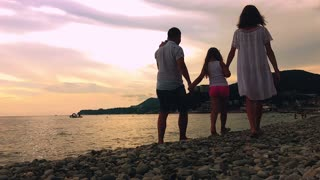 Family going to the beach in slow motion. Baby's first steps on the sea shore.