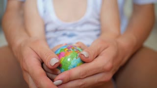 Family holding the globe in his hands. Concept of travel and earth day holiday.