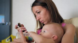 family, technology, motherhood and people concept - happy mother with little baby boy lying on sofa and smartphone at home