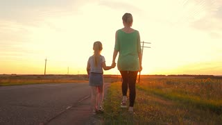 Family walking on the evening road during sunset. Child with mom.