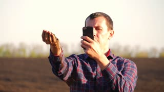 Farmer take a sample of the black fertile soil. Farmer handful of fertile soil standing in cultivated field. Soil, Agriculture, - Farmer hands holding and pouring back organic soil.